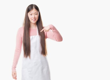 Young Chinese shop owner woman over isolated background wearing white apron with surprise face pointing finger to himself