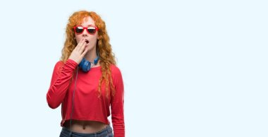 Young redhead woman wearing headphones cover mouth with hand shocked with shame for mistake, expression of fear, scared in silence, secret concept