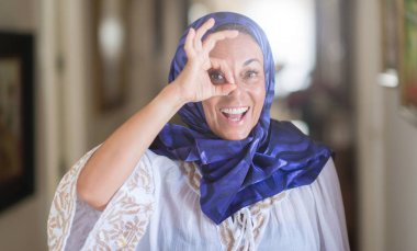 Middle age brunette arabian woman wearing colorful hijab with happy face smiling doing ok sign with hand on eye looking through fingers