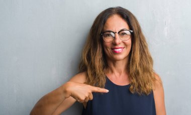 Middle age hispanic woman over grey wall wearing glasses with surprise face pointing finger to himself