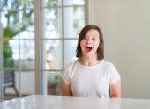 Fotografie Down syndrome woman at home scared in shock with a surprise face, afraid and excited with fear expression