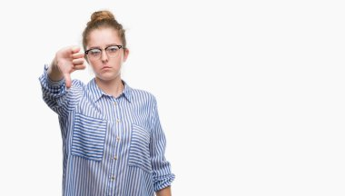 Young blonde business woman looking unhappy and angry showing rejection and negative with thumbs down gesture. Bad expression.