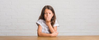 Young hispanic kid sitting on the table at home looking stressed and nervous with hands on mouth biting nails. Anxiety problem.
