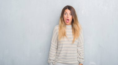Young adult woman over grunge grey wall wearing winter sweater afraid and shocked with surprise expression, fear and excited face.