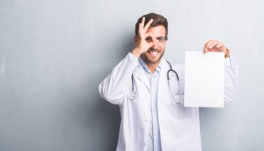 Handsome young doctor man over grey grunge wall holding blank sheet contract with happy face smiling doing ok sign with hand on eye looking through fingers