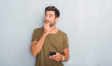 Handsome young man over grey grunge wall texting a message using smartphone serious face thinking about question, very confused idea