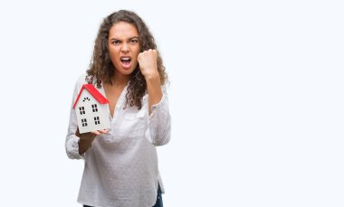Young hispanic real state agent woman holding small house annoyed and frustrated shouting with anger, crazy and yelling with raised hand, anger concept