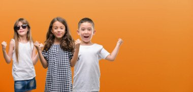 Group of boy and girls kids over orange background screaming proud and celebrating victory and success very excited, cheering emotion