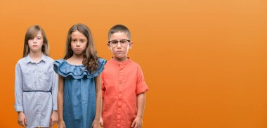 Group of boy and girls kids over orange background with a confident expression on smart face thinking serious