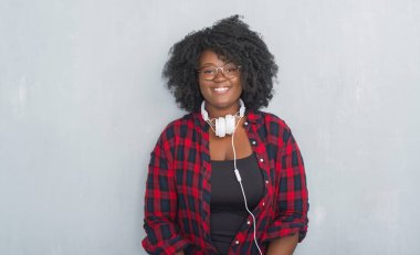 Young african american woman over grey grunge wall wearing headphones with a happy and cool smile on face. Lucky person.