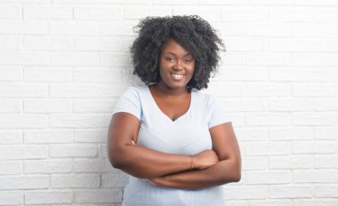 Young african american plus size woman over white brick wall happy face smiling with crossed arms looking at the camera. Positive person.