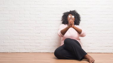 Young african american woman sitting on the floor at home begging and praying with hands together with hope expression on face very emotional and worried. Asking for forgiveness. Religion concept.