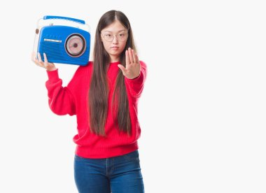 Young Chinese woman over isolated background holding vintage radio with open hand doing stop sign with serious and confident expression, defense gesture