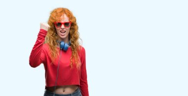 Young redhead woman wearing headphones annoyed and frustrated shouting with anger, crazy and yelling with raised hand, anger concept