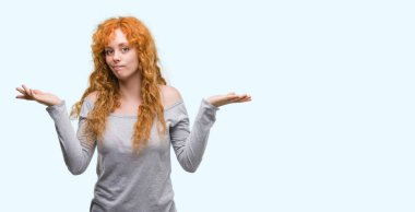 Young redhead woman clueless and confused expression with arms and hands raised. Doubt concept.