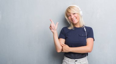 Adult caucasian woman over grunge grey wall wearing headphones very happy pointing with hand and finger to the side