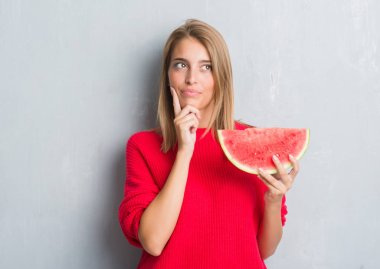 Beautiful young woman over grunge grey wall eating water melon serious face thinking about question, very confused idea