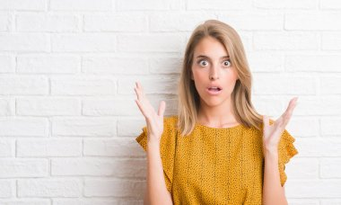 Beautiful young woman over white brick wall scared in shock with a surprise face, afraid and excited with fear expression
