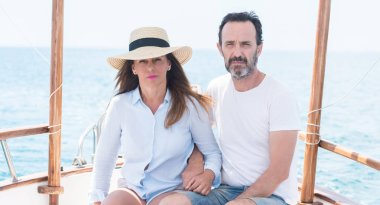 Middle age couple traveling on sailboat with a confident expression on smart face thinking serious