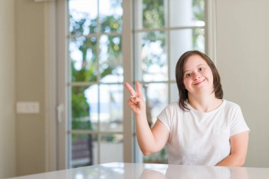 Down syndrome woman at home smiling with happy face winking at the camera doing victory sign. Number two.