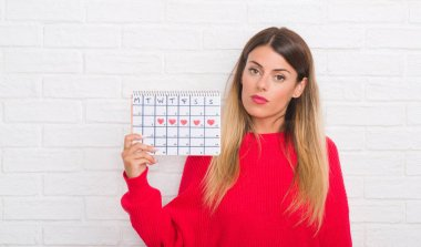 Young adult woman over white brick wall holding period calendar with a confident expression on smart face thinking serious