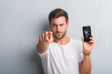 Handsome young man over grey grunge wall showing broken smartphone screen pointing with finger to the camera and to you, hand sign, positive and confident gesture from the front