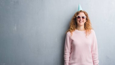 Young redhead woman over grey grunge wall wearing birthday cap with a happy face standing and smiling with a confident smile showing teeth