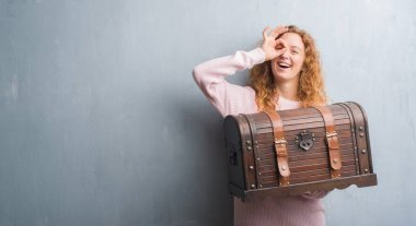 Young redhead woman holding vintage chest with happy face smiling doing ok sign with hand on eye looking through fingers