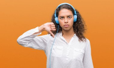Young hispanic woman wearing headphones with angry face, negative sign showing dislike with thumbs down, rejection concept