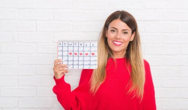Young adult woman over white brick wall holding period calendar with a happy face standing and smiling with a confident smile showing teeth