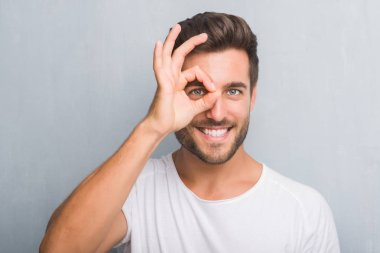 Handsome young man over grey grunge wall with happy face smiling doing ok sign with hand on eye looking through fingers
