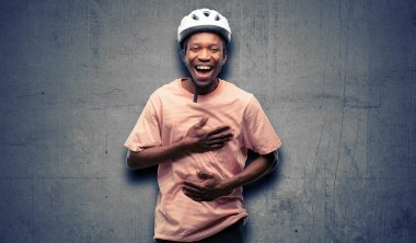 Black man wearing bike helmet confident and happy with a big natural smile laughing