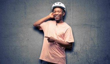 Black man wearing bike helmet pointing away side with finger