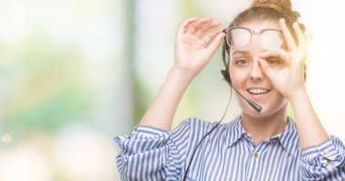 Young blonde call center operator woman with happy face smiling doing ok sign with hand on eye looking through fingers