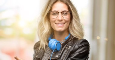 Young student woman with headphones holding something in empty hand