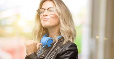 Young student woman with headphones proud, excited and arrogant, pointing with victory face