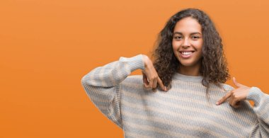 Beautiful young hispanic woman wearing stripes sweater looking confident with smile on face, pointing oneself with fingers proud and happy.