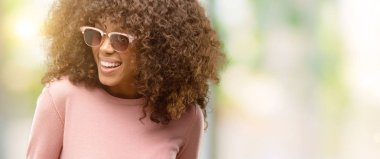 African american woman wearing pink sunglasses looking away to side with smile on face, natural expression. Laughing confident.
