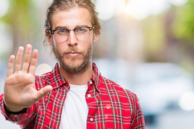 Young handsome man with long hair wearing glasses over isolated background doing stop sing with palm of the hand. Warning expression with negative and serious gesture on the face.
