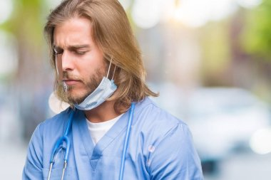 Young handsome doctor man with long hair over isolated background with hand on stomach because nausea, painful disease feeling unwell. Ache concept.