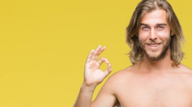 Young handsome shirtless man with long hair showing sexy body over isolated background smiling positive doing ok sign with hand and fingers. Successful expression.