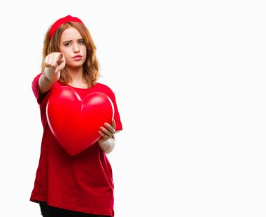 Young beautiful woman holding red heart in love over isolated background pointing with finger to the camera and to you, hand sign, positive and confident gesture from the front