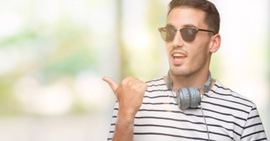 Handsome young man wearing headphones smiling with happy face looking and pointing to the side with thumb up.