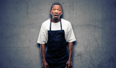 African man shop owner wearing apron scared in shock, expressing panic and fear