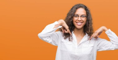 Beautiful young hispanic woman looking confident with smile on face, pointing oneself with fingers proud and happy.