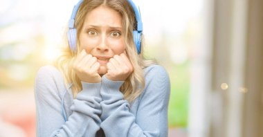Young beautiful woman listening to music terrified and nervous expressing anxiety and panic gesture, overwhelmed