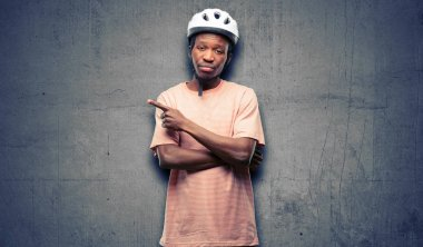 Black man wearing bike helmet pointing away side with finger