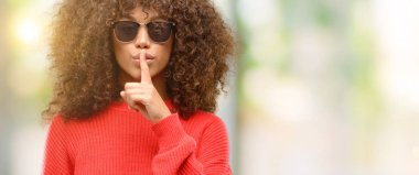 African american woman wearing sunglasses with index finger on lips, ask to be quiet. Silence and secret concept