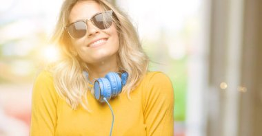 Young beautiful woman with headphones thinking and looking up expressing doubt and wonder