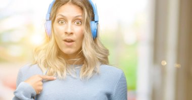 Young beautiful woman listening to music happy and surprised cheering expressing wow gesture, pointing with finger